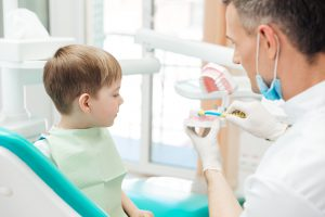 Dentist educating little boy about brushing teeth in clinic
