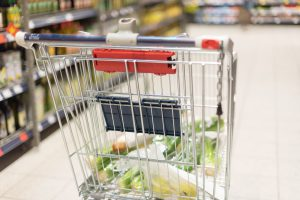 Grocery shopping cart full with food at blurred supermarket background. Copy space. Sustainable